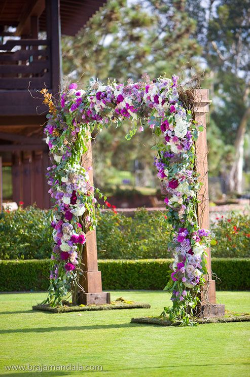 A gorgeous wooden arbor is covered in fresh purple and pink blooms and green ivy.