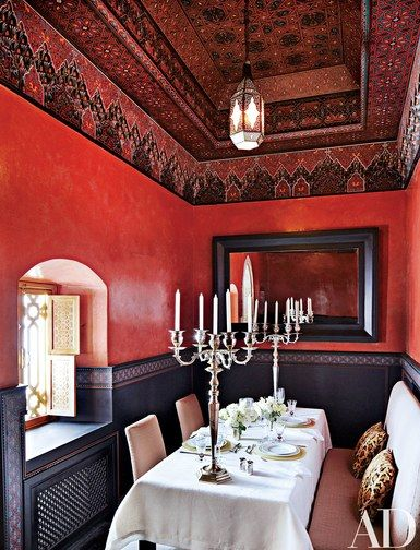 A hand-carved and -painted ceiling crowns the dining room; the silver candelabra were found at a Paris flea market | archdigest.com