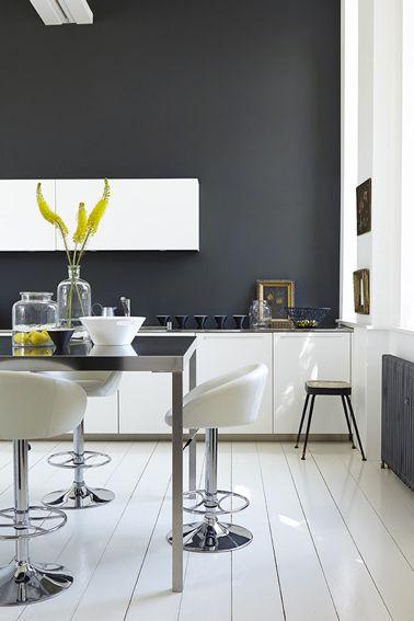 On aime les touches de doré et de jaune dans cette cuisine design où la peinture gris anthracite sur le mur sublime le linéaire de meubles laqués blanc