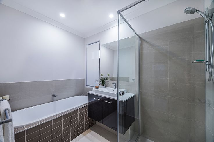 #Bathroom #style ideas from #Ausbuild's Bellfield display #home. www.ausbuild.com.au. This #Bathroom presents a clear, chic look, with a glass #shower #door and fresh white #walls. The #tiled #bathtub is an inviting shade of espresso.