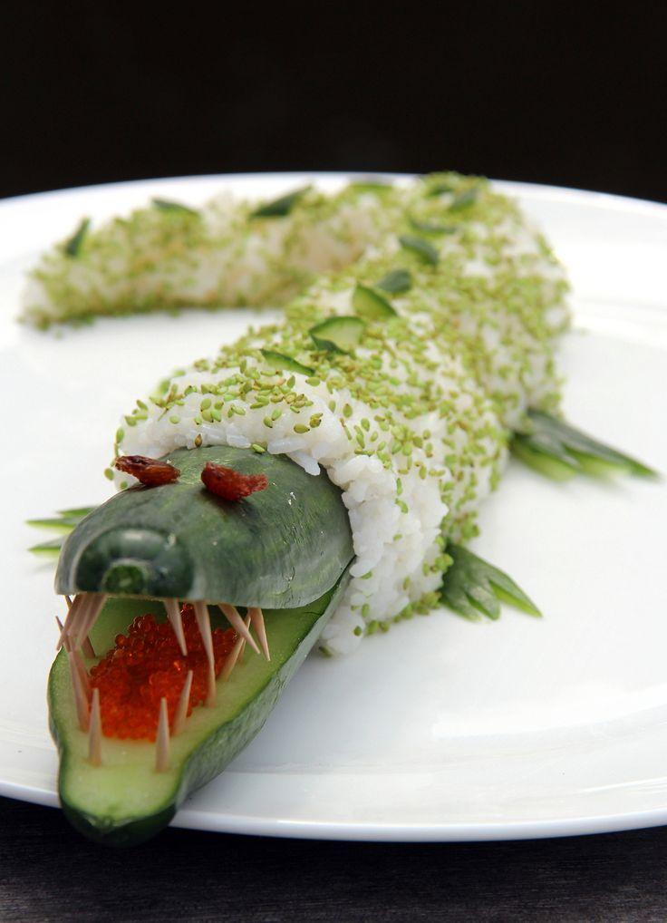 'Sushi - krokodil' .............................! Snijd de komkommer een klein stukje doormidden. Knip met een schaar van tandenstokers kleine puntjes af en steek ze als tanden in de bek van de krokodil. Gebruik voor de tong een laagje tobiko. Snijd achter de kop van de komkommer rondom een dun laagje af. Van deze schil maak je de 4 pootjes en wat schubben. Hierna breng je een laagje sushirijst aan. Bestrooi het dan wat met wasabi-sesamzaadjes. Steek 2 rozijnen in de kop. www.sushiles.nl