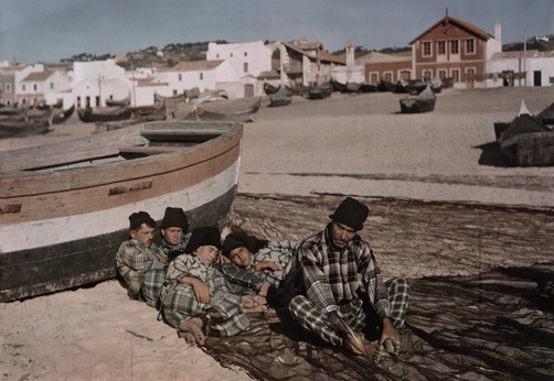 Autochrome: W. Robert Moore. Four men rest beside a fishing boat while one man mends a net. Nazare, Leiria, Portugal.