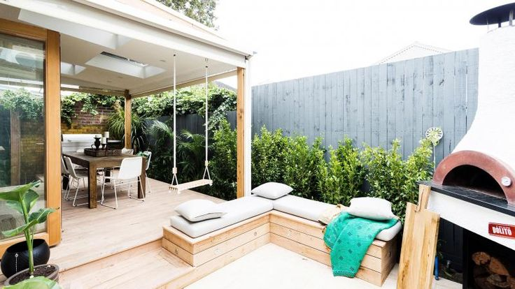 Reno Rumble: Jess & Ayden's outdoor entertaining area with pizza oven, decking, built-in seats, roof with skylights, swing, garden bed