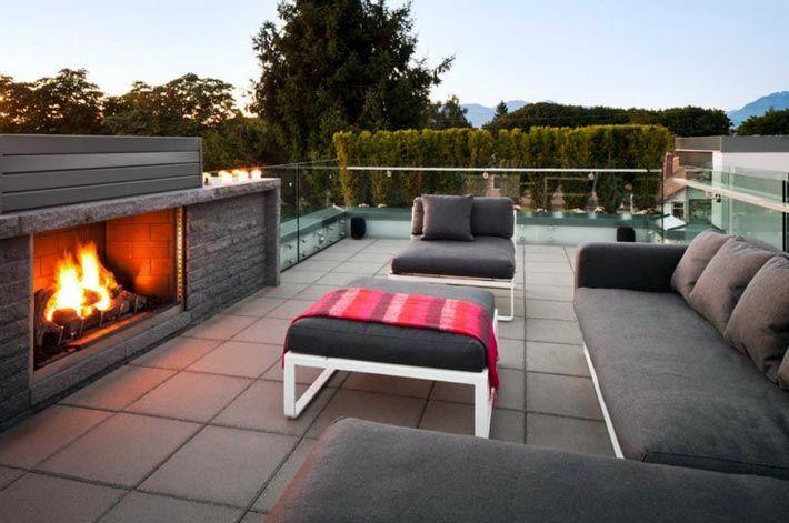 Терраса на крыше с камином и большим диваном