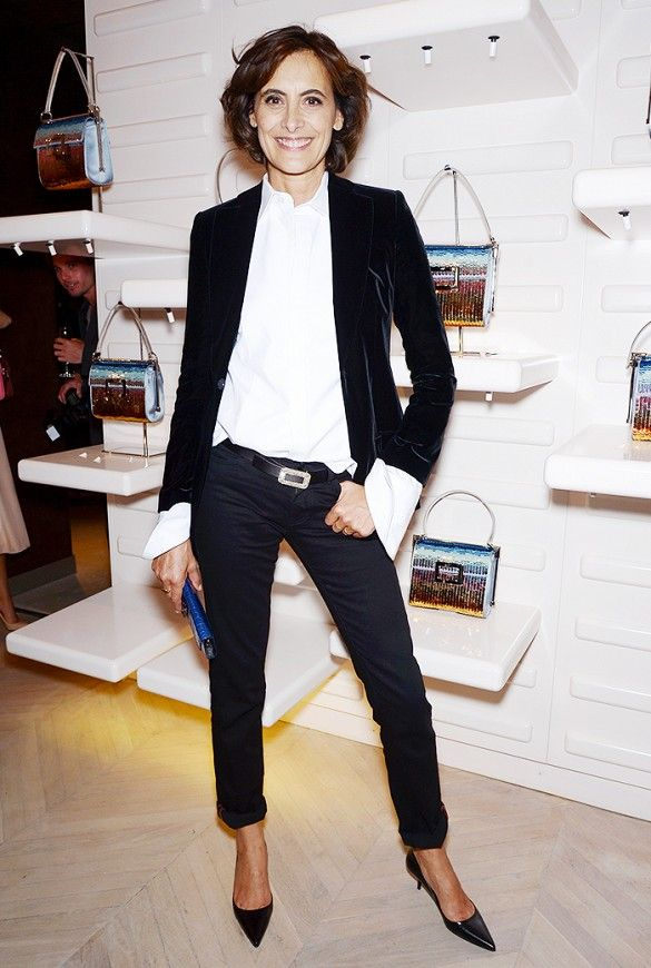 Ines de la Fressange wears a white button-down top, velvet black blazer, black skinny jeans, black kitten heels, and a blue clutch
