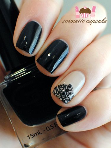Black nails with black lace stamp on a nude accent nail.