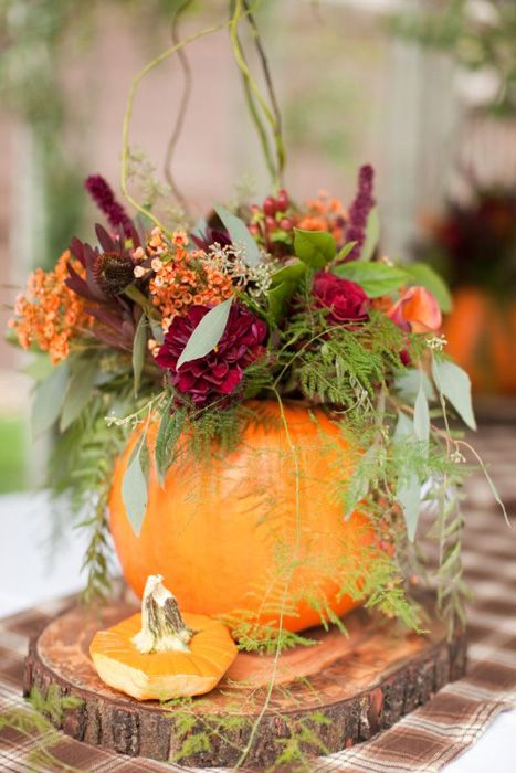A hollowed out pumpkin as a vessel for a beautiful bouquet of flowers