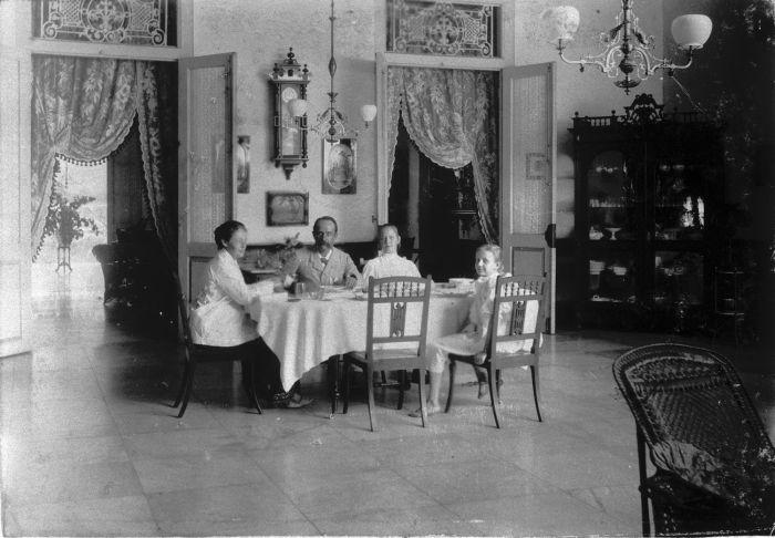 COLLECTIE_TROPENMUSEUM_Portret_van_een_gezin_aan_tafel_tijdens_een_maaltijd_TMnr_60008784.jpg (700×486)