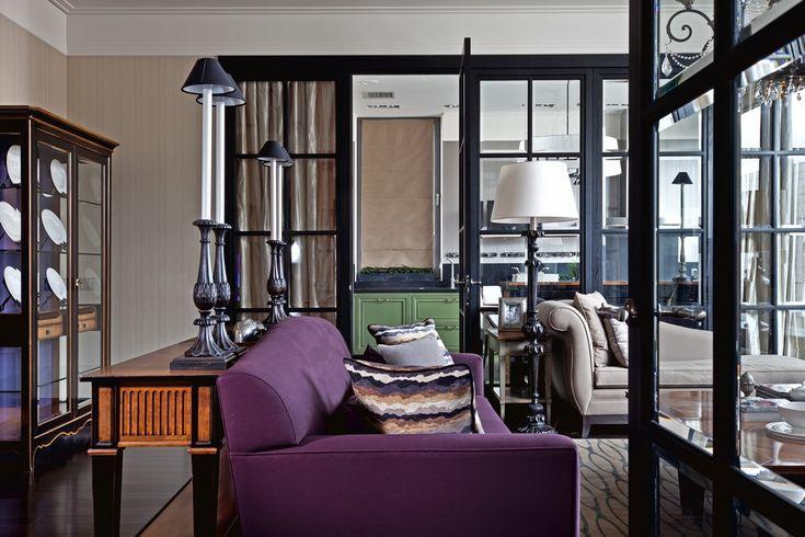 Сочно-фиолетовый диван Maries Corner в гостиной и салатный гарнитур Zonta на кухне — главные цветовые акценты интерьера, которые особенно эффектно смотрятся на фоне темных полов и пастельных стен. Настольные лампы — Chelini.