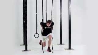 Výpady vzad na jednej nohe s výskokom a príťahom kolena k hrudi v predklone na kruhoch