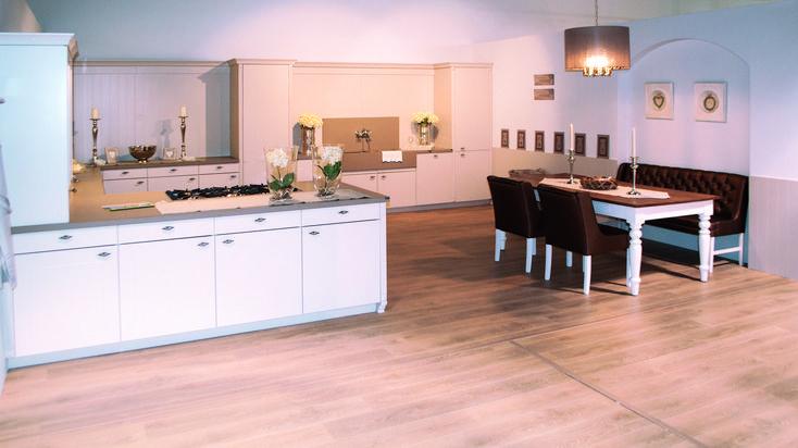 Landelijke keuken in Toscaanse stijl. In deze grote keuken wordt gezelligheid gecreëerd zowel de opstelling en materialen van de keuken,als door de zitbank en de landelijke tafel. De deuren van de keukenkastjes zijn uitgevoerd in lak en hebben een mooie witte kleur die in contrast staat met de donkere zitbank. De massieve spoelbak springt ook meteen in het oog en zorgt voor die landelijke toets.