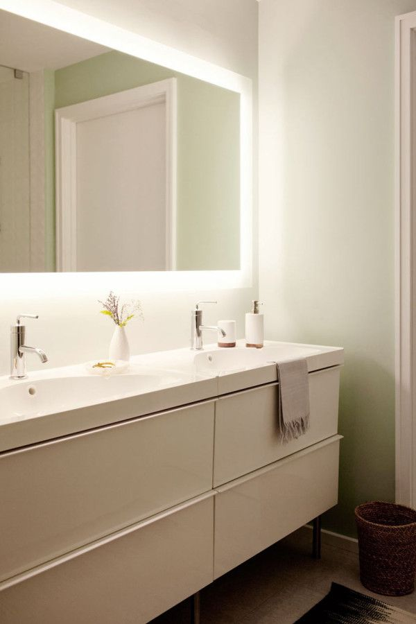 The bathroom was outfitted with IKEA Godmorgon cabinets and Porcelanosa tile, continuing the modern, polished look of the rest of the condo. An electric mirror brings more light into the once dark space.