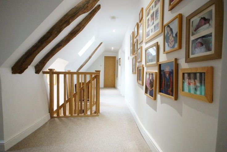 Upstairs landing with family photos and solid oak banister. Original beams exposed.