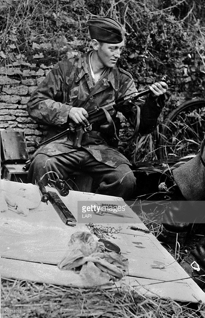 World War II. Front of Normandy, July 1944. German soldier of the Luftwaffe cleaning his submachine gun Bergmann. Pin by Paolo Marzioli