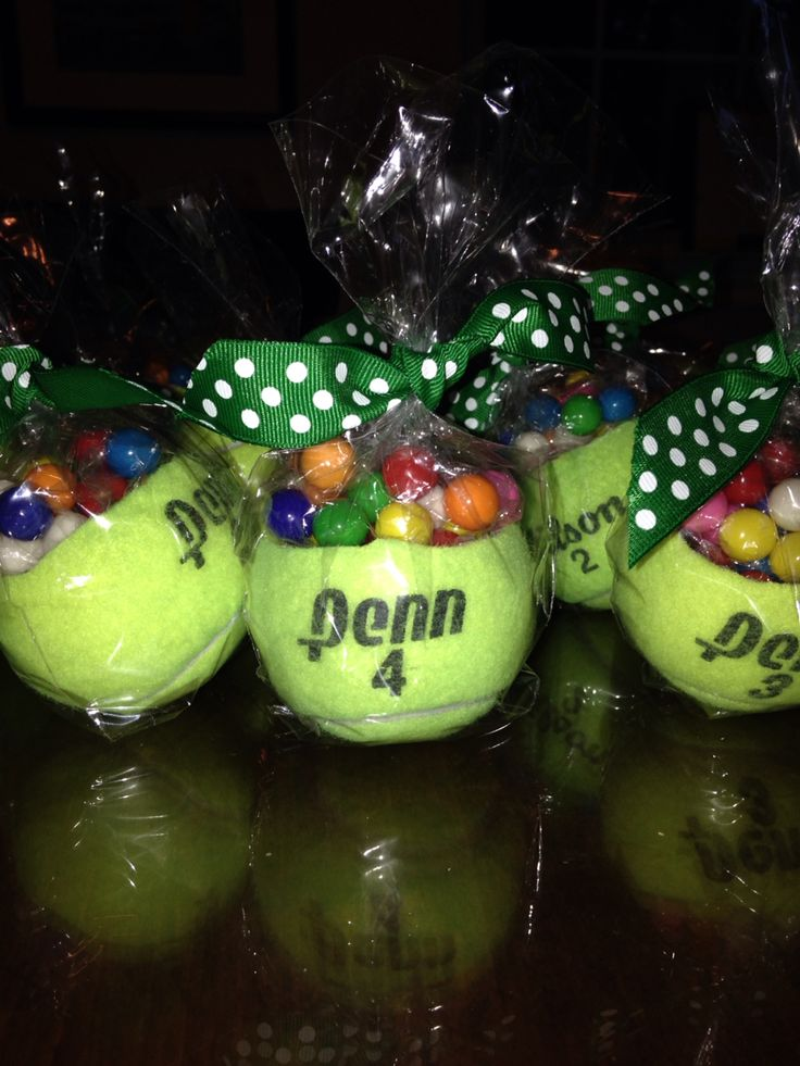 Tennis Ball Gift Favors for a tennis themed high school graduation party. To make: Have a very helpful husband cut tops of ball off with a utility knife, fill 4x6 treat bags with 2 oz of mini gum balls, tie the bags and put top end inside the ball, put tennis ball inside a larger gift bag and tie with ribbon.
