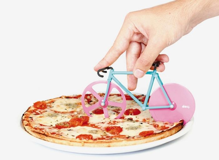 Cut Your Pie In Style: Fixie Bike Pizza Cutter. What's not to love? It's made of what appears to be thin plastic and has little grooves where cheese and sauce can dry and harden--how fun! Plus, you finally get to live the American Dream of your fingers riding a tiny bike across a pizza.
