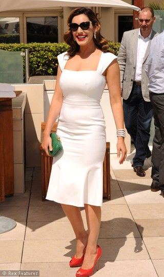Kelly Brook match reds shoes, a green bag and figure hugging white dress. Summer with style.
