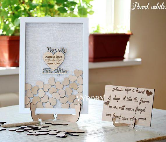 Bienvenue amis! Ce livre d'or pour un mariage, alternatif drop zone supérieure dans un cadre blanc avec un coeur en bois Happily Ever After. Le livre d'or rustique signe avec vos noms. Le livre d'or exclusif est fait pour vous. L'ensemble comprend un cadre personnalisé en blanc et petits