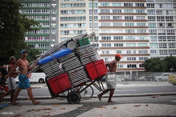 A vendor transports beach chairs on Copacabana beach on July 28, 2015 in Rio de Janeiro, Brazil. The famed beach will host various Olympic events including beach volleyball, cycling, open water marathon and triathlon. August 5 marks the one-year mark to the start of the Rio 2016 Olympic Games.