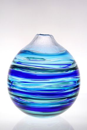 In this stunning bowl from Cal Breed, of Orbix Hot Glass, the artist was able to capture the fluidity of water in blown glass. This beautiful, layered bowl uses dark and light blue glass to created a gorgeous layered look with a silver metallic-like top