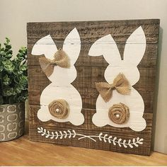 Think Spring! This adorable dual bunny hand-painted on a reclaimed wood plank sign makes for the perfect Easter and Spring décor. Rustic, simple, and cute!  Each sign is unique due to the natural variation of grain and knots in the wood. Approximate size is 12x12 and includes a natural jute rope for hanging. Each bunny has a handmade tail and bow/bowtie made of burlap. **Please note, due to the use of reclaimed wood in the making of this sign, color variation, knots, and grain may vary. ...