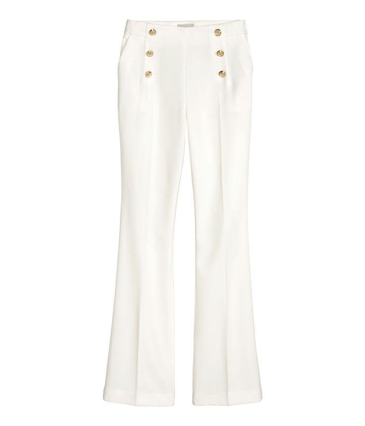 Hvit. En bukse i vevd kvalitet med utsvingte ben. Buksen har høy midje og dekorative knapper foran. Sidelommer og fuskelommer bak. Skjult glidelås i den ene
