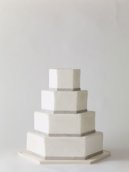 A Hexagonal Tiered Cake  Round and square aren't the only options when it comes to tier shapes, hexagonal tiers are a creative twist on the traditional white cake and silver metallic bands are eye-catching. Cake by Ana Parzych Cakes