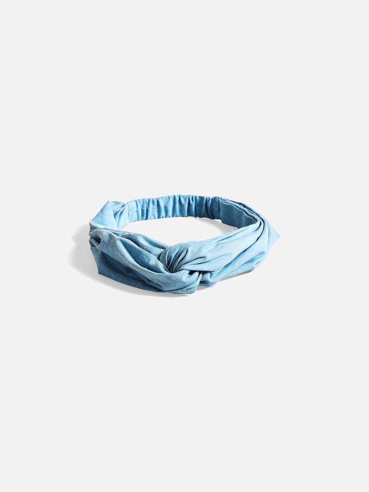 Hodebånd i stoff med strikk i nakken.  Blå