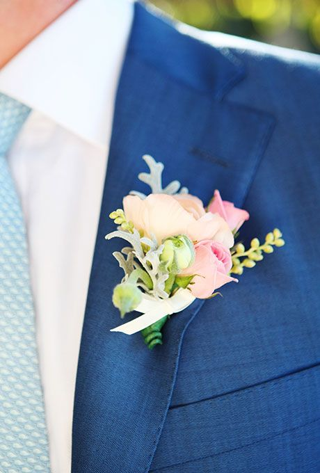Brides: Colorful Boutonniere with Peach & Pink Roses. A boutonniere of muted pink, peach, and green flowers, including Annabelle roses, dusty miller, and greenery, created by Cattleya Flowers.