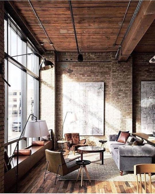 Industrial living room with high ceilings, a brick wall, and huge windows.