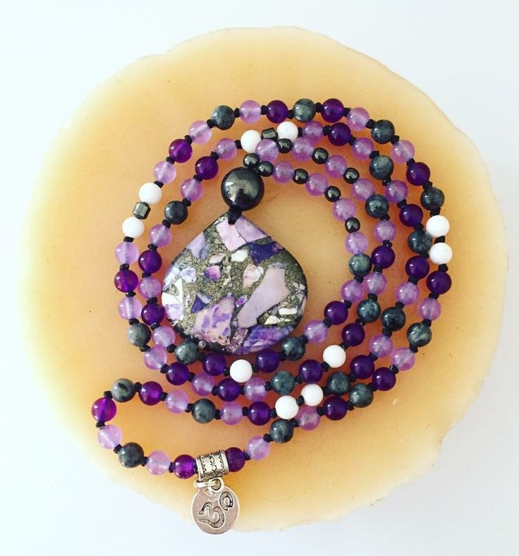 """108 bead hand-knotted Mala with 4mm Magnetic Hematite, 6mm Alexandrite, Amethyst, Labradorite and Tridacna Shell beads. The guru is a 12mm Hematite bead and the focal, a beautifully unique Sea Sediment Jasper stone. Has an Om charm on the back and hangs at just over 17"""" so is a shorter, more delicate Mala!"""