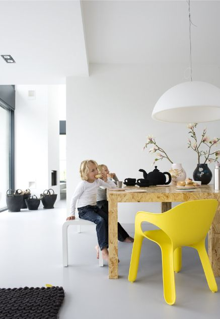 Funky yellow chair in a white dining room