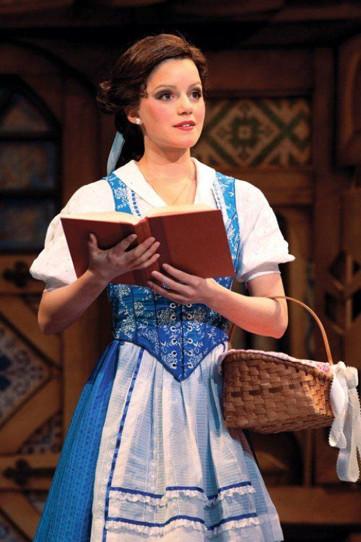 Another Broadway shot shows they changed from a blue dress to more of a two-piece look with a bustier and skirt.  The apron does not tie over the dress, but rather the bustier extends past it, so it looks like it's sewn right into the costume.  They