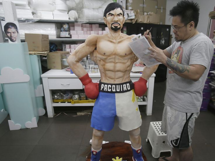 Zach Yonzon, owner of The Bunny Baker cafe, puts finishing touches on the life-size cake of Filipino boxer Manny Pacquiao in Quezon, Manila.  Bullit Marquez, AP