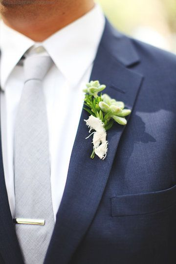 boutonnière of small succulents and a bit of greenery tied with raw muslin.
