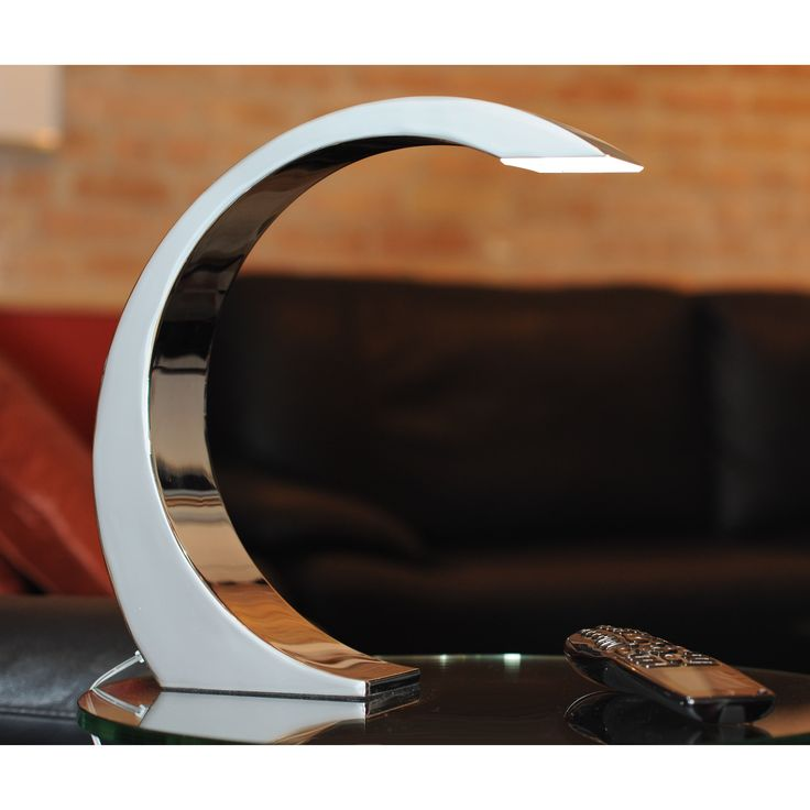 This contemporary table lamp features an LED touch light. The desk lamp has a polished stainless steel finish and an ultra-modern silhouette. It gently arcs over your table to shine light down on whatever you are working on.