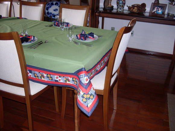 Toalha de mesa confeccionada em tecido 100% algodao, na cor verde, com barrado estampado em vermelho, verde, marinho e vermelho. Acabamento em viés vermelho e marinho.