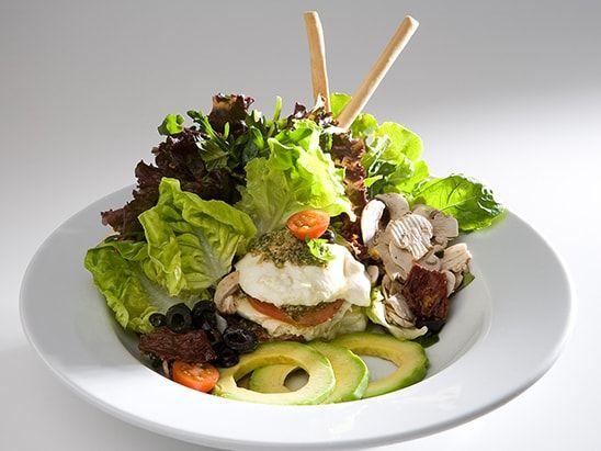 Variedad de lechugas frescas, aceitunas negras, tomates frescos, champiñones y tomates secos con queso mozzarella, pesto aguacate, vinagre balsámico y aceite de oliva.