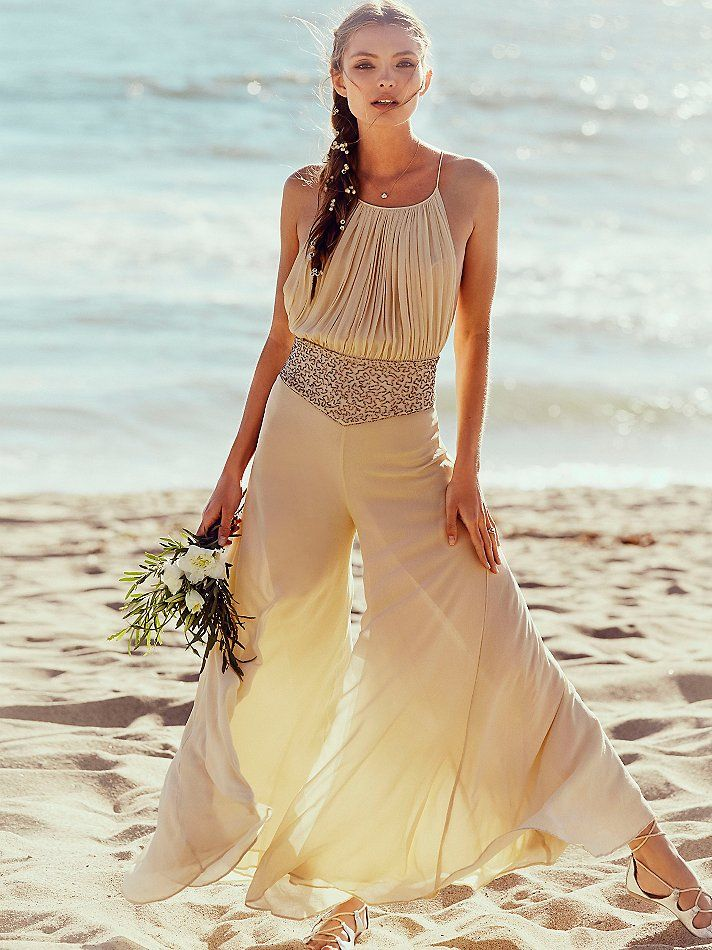 Kristal's One Piece | Silk chiffon one piece with a pleated bodice and elegant, wide-leg silhouette. Stunning beadwork defines a narrow waist. Open back features delicate straps and tiny button closures.   *By Free People   *Leave them breathless. This exclusive capsule of dreamy and ethereal wedding dresses was created for the romantic bride by a Free People designer.    *Champagne   *One Piece   *Open Back   *Button Closures   *Beadwork