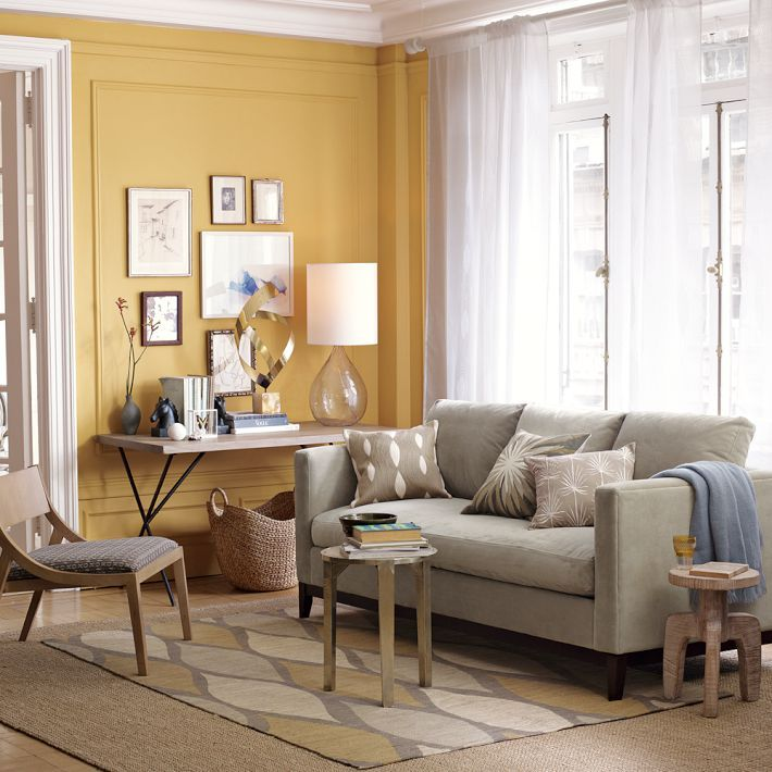 Love this yellow accent wall and grey couch - West Elm