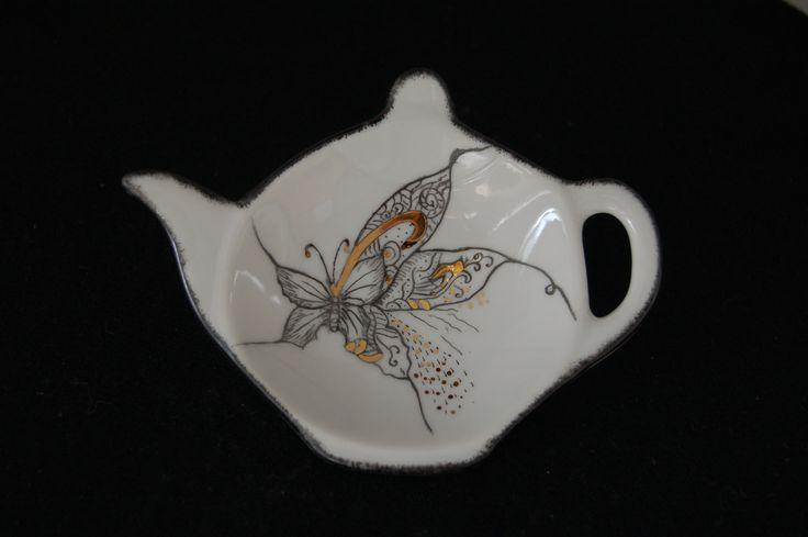 Petit repose sachet de thé en forme de théière décoré avec un travail à la plume et pose de quelques points d'or........ Un motif fleurs assorti au petit sucrier Un deuxiè - 17273213