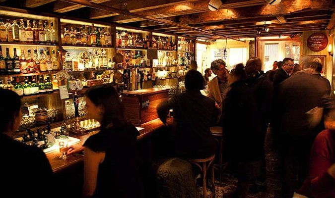 Bar tour in NY - People drinking at a dimly lit prohibition bar called The Dead Rabbit