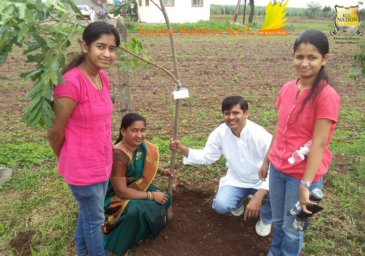 A Family Planting a tree during Tree Plantation Event organized by Kumar Builders KUL on Independence Day.