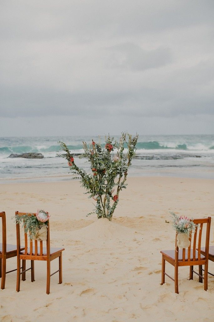 A Blooming Brilliant Beach Wedding created by Jessica for Nicole and Hector including an abstract floral and foliage arbour, and flowers for chairs in rustic jars covered with burlap.