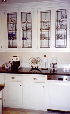 White inset kitchen cabinets, black granite countertops and white subway tile offset beautiful, antique-style lead glass cabinet doors with a tulip design.