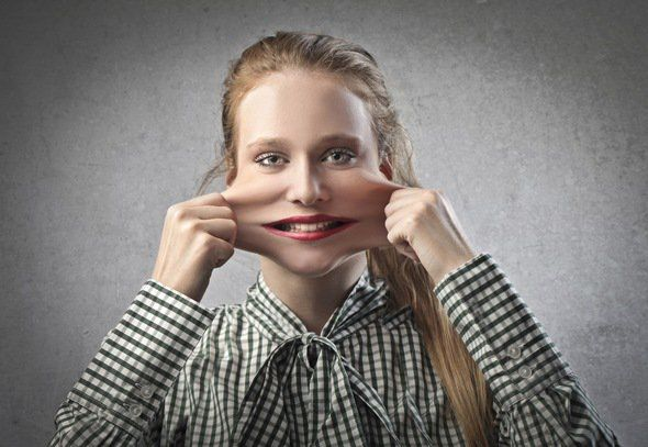 Young Woman Stretching the Skin on Her Face with Both Hands