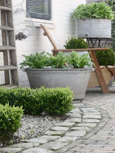 Large galvanized pot with herbs or flowers, stone edging with gravel and pavers.