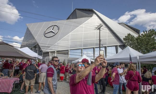 Mike Vivas, center, from Atlanta takes a selfie at a tailgate party across the street from the new Mercedes-Benz Stadium where the…