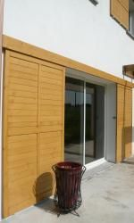 Exemples de réalisations de chantiers de fermetures bois, portes et volets bois sur-mesure Volet coulissant en bois pour maison individuelle traditionnelle. - (69100 Villeurbanne)