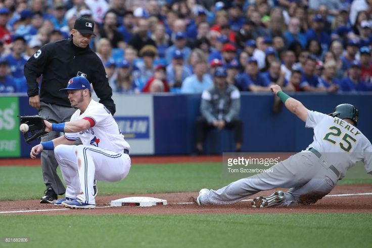 Ryon Healy #25 of the Oakland Athletics slides safely into third base in the first inning during MLB game action as Josh Donaldson #20 of the Toronto Blue Jays takes the throw at Rogers Centre on July 24, 2017 in Toronto, Canada.